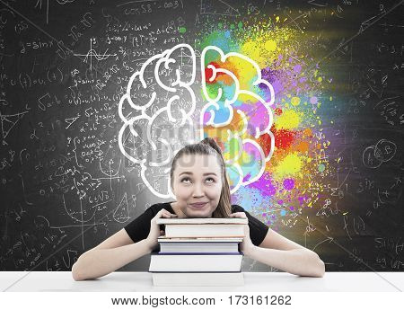 Portrait of a girl with a ponytail sitting at her desk with her head resting on a stack of book. There is a brain sketch drawn on a blackboard behind her.