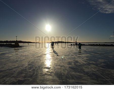 Frust strand med skridskoråkare och solen på klarhimmeln