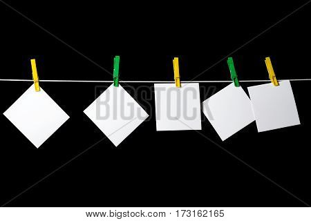 blank sheets of paper attached to a rope clothespins