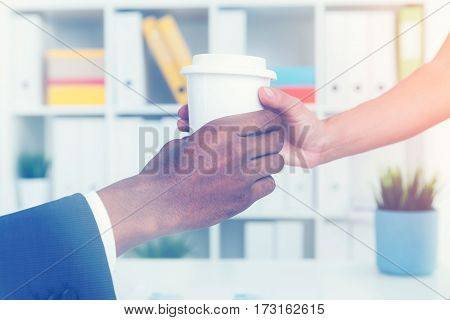 Close up of a hand of a woman giving a paper cup of coffee to her boss sitting at the table. Toned image.