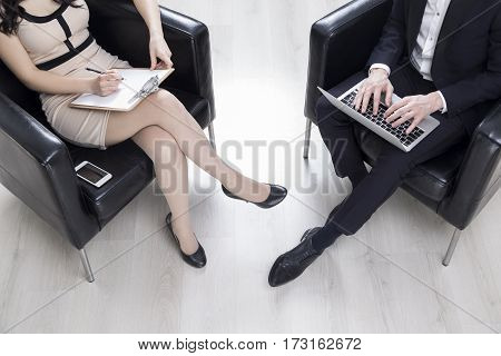 Woman Writing In Clipboard, Man Typing
