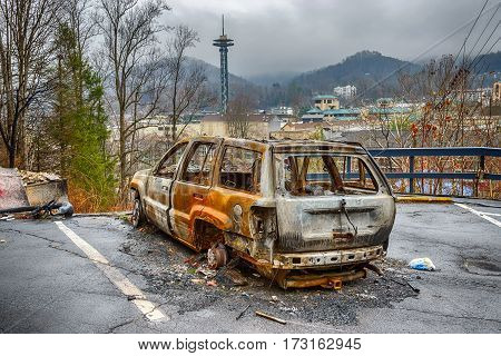 GATLINBURG TENNESSEE/USA - DECEMBER 14 2016: A gutted carcass is all that remains of a car in the aftermath of a forest fire that destroyed part of Gatlinburg TN in late 2016.