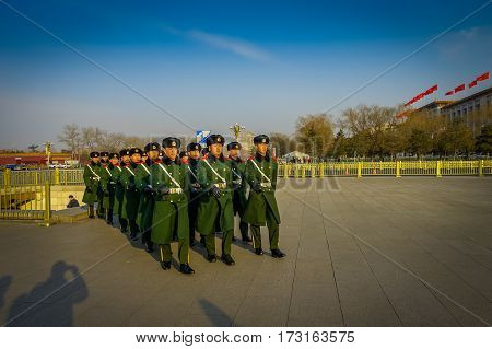 BEIJING, CHINA - 29 JANUARY, 2017: Chinese army soldiers marching on Tianmen square wearing green uniform coats and black hats, beautiful blue sky.