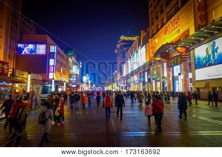 BEIJING, CHINA - 29 JANUARY, 2017: Walking on the famous pedestrian shopping street Wangfujing on a dark evening, busy city everyday life.