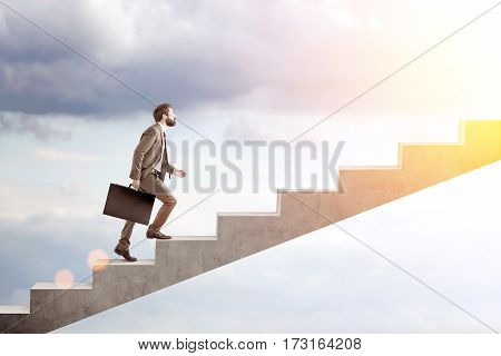 Side view of a bearded man in a suit climbing stairs to the sky. Concept of a road to success in business.