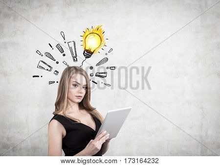 Portrait of a businesswoman with a tablet computer standing near a concrete wall with exclamation marks and a yellow light bulb sketch drawn on it. Mock up