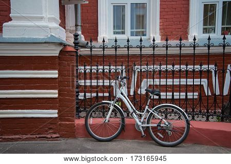 Bike stands on the street beside the red house