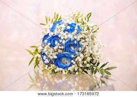 Beautiful wedding bouquet of blue and white flowers on the glass table