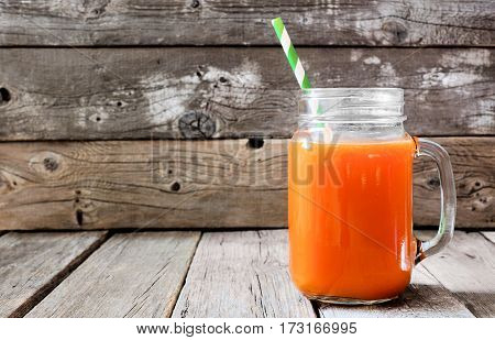 Healthy carrot juice in a mason jar glass over a rustic wood background
