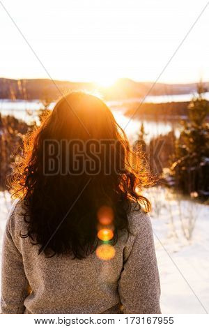 Young brunette woman in grey pullover looking in the sunset
