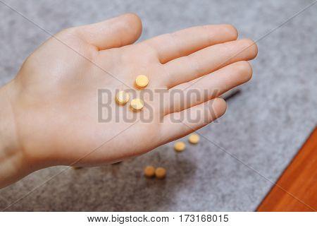 Taking medicine pills in hand, an analgesic, to treat disease
