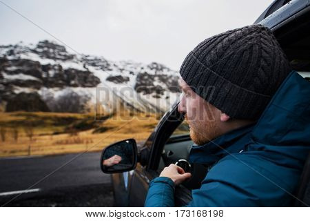 Young red-haired man is looking outside his car window on beautiful snow covered mountains in Iceland. Road travel adventure