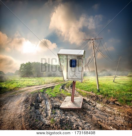 Old payphone on a road in the field