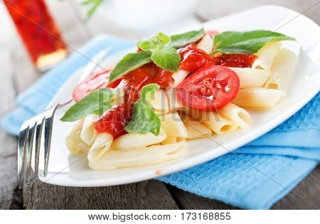 Pasta with sauce and tomatoes on a wooden table
