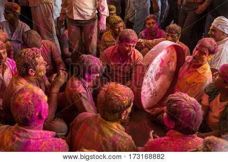 Barsana, India - March 17, 2016: Devotees play music covered with colors during the Holi celebration in Barsana, India. Holi is the most celebrated religious festival in India.