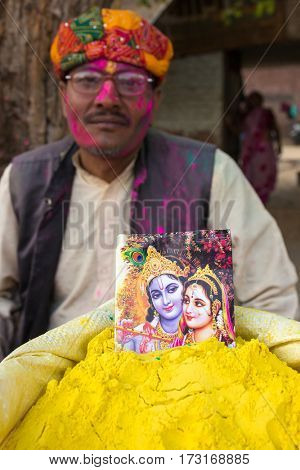 Barsana, India - March 17, 2016: Unidentified man sell powdered dyes used for Holi festival in India