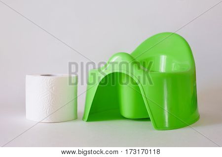 Child's green training pot and roll of toilet paper on a white background.