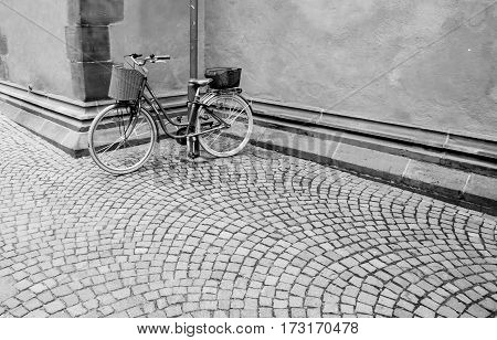 Old styled Bicycle with basket parking near street. Chained black bike in the corner outside the building