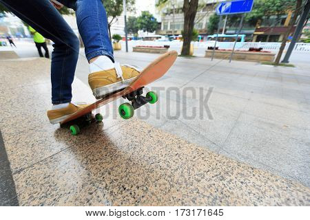 young skateboarder legs riding skateboard at city skatepark
