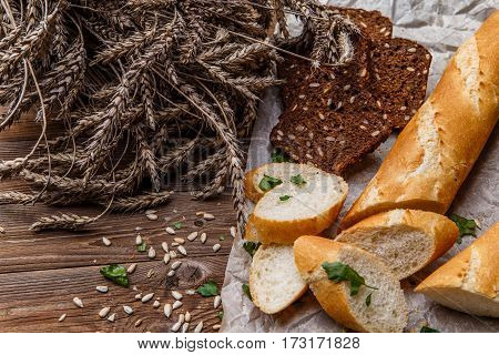 Baguette with grain bread on table with wheat, sunflower seeds