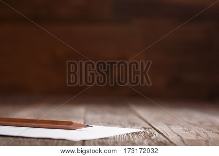 white paper with a pencil laying on a wooden table horizontal. Brown background. Brown wooden pencil. Education and school. Design and art.
