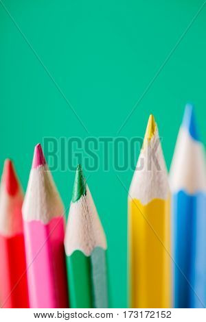 Macro view of crayons. Colored Pencils. Colored pencils on green background. Art and design. Painting and drawing. School and education. Artist.