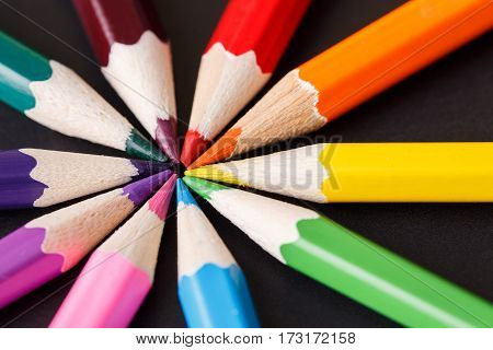 concept selection options with pencils on dark background top view. Circle of the colorful pencils. One center. Painting and drawing. Art and design. Tips pencils.