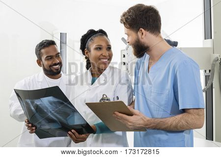 Medical Professionals With Chest X-ray And Clipboard In Hospital