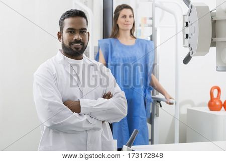 Male Radiologist Standing Arms Crossed In Examination Room