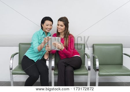 Smiling Patient's Using Digital Tablet While Sitting At Hospital