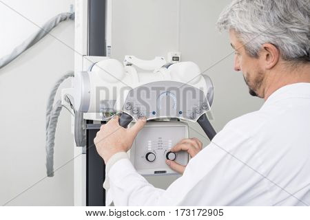 Male Radiologist Adjusting The Controls On X-ray Machine