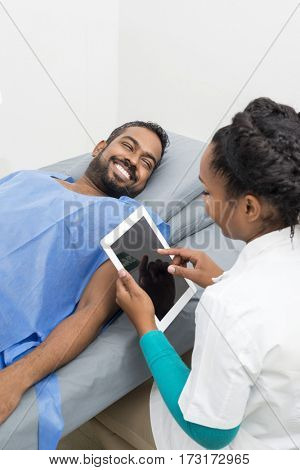 Radiologist Using Digital Tablet By Patient Lying On Hospital Bed