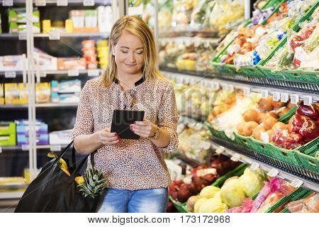 Customer Using Digital Tablet While Shopping In Grocery Store