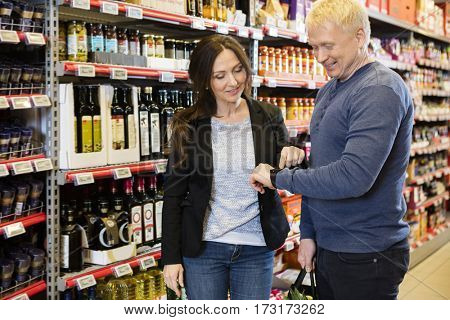 Smiling Couple Using Smart Watch In Grocery Store