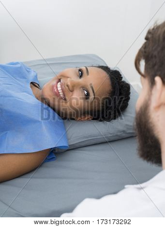 Woman Looking At Male Doctor While Lying On Bed