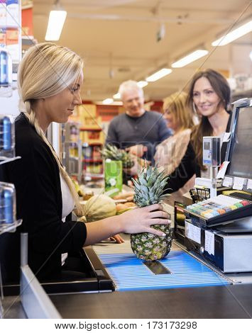 Cashier Making Bills While Customers Standing At Checkout Counte