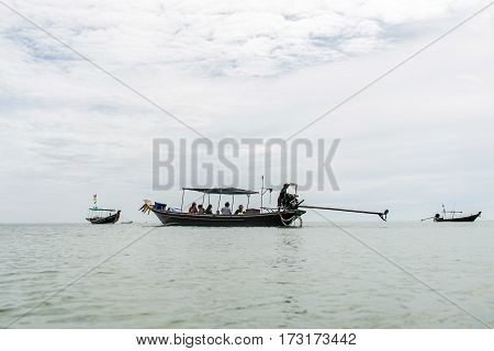 Thai traditional longtail boat with big diesel engine in action smoke pollution