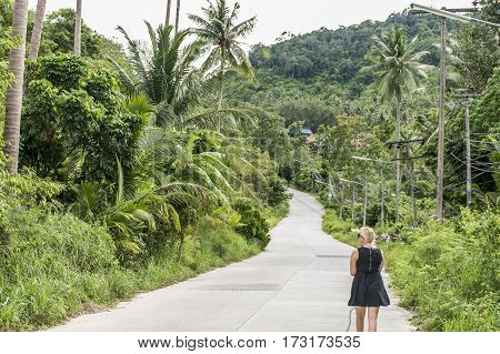 Young girl walking alone on mountain road in the jungle in Thailand Koh Phangan