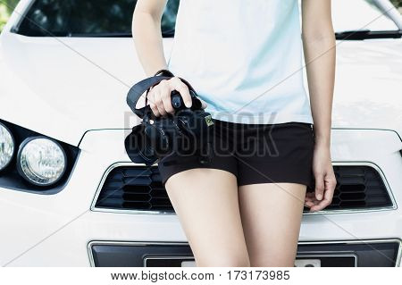Photographer woman holding camera in fornt of the car.