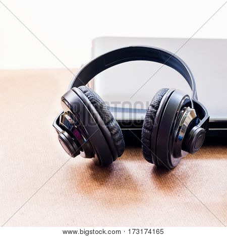 Headphones and laptop on wood floor background.
