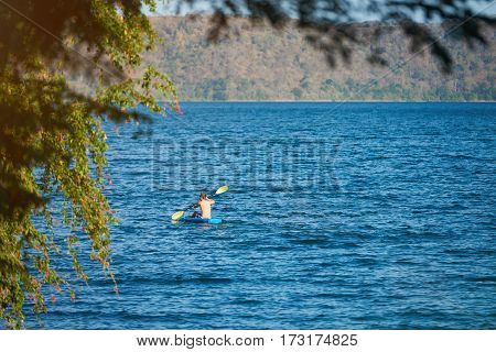 Man doing kayak in lagoon on sunny day. Kayak activity in wide blue lagoon water
