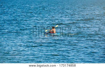One man on blue kayak in deep lake water around. Kayak activity with copyspace around