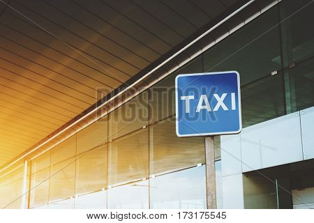 Billboard with TAXI caption with copy space area for your text message or promotional content taxi road sign near cabstand and windowed facade of airport or mall entrance on sunny day