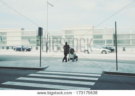 Rear view of man with luggage cart standing near airport zebra traffic cross way silhouette of experienced male with several suitcases waiting for taxi outdoors near airport terminal in Barcelona