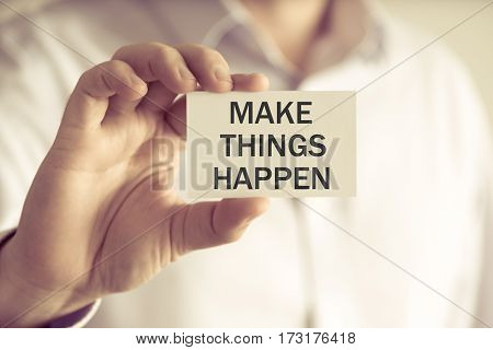 Businessman Holding Make Things Happen Message Card