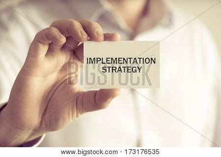 Businessman Holding Implementation Strategy Message Card