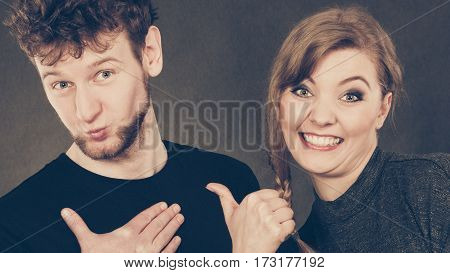 Portrait Of Joyful Couple Pointing To Man.
