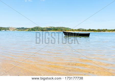 Blue dinghy afloat on peaceful calm Ngunguru estuary in summer holiday destination Northland New Zealand