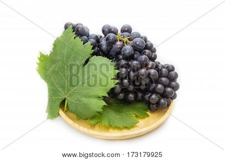 Black grapes bunch isolated on wooden plate and white background with green leaf package design element