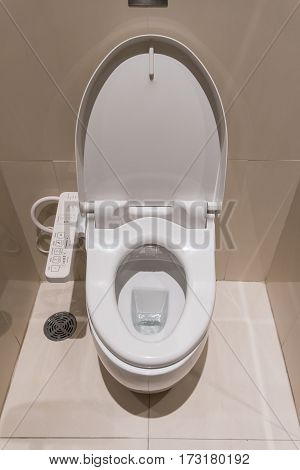 white flush toilet with electronic control in modern bathroom interior